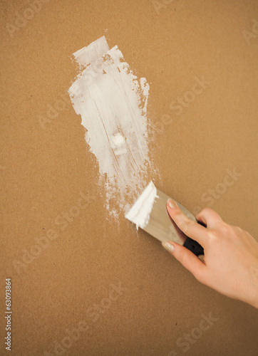 Closeup photo of hand working with spatula and plaster
