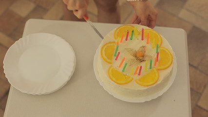 Woman cuts the cake with candles and oranges Full HD 1080 NTSC