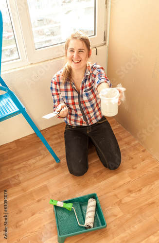 Portrait of smiling woman with putty, spatula and paint roller