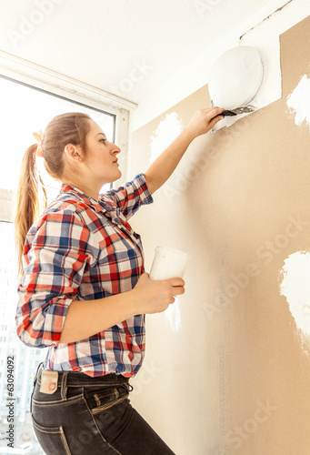 Closeup portrait of young woman aligning gypsum cardboard