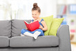 Cute little girl reading a book in the living room
