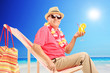 Mature man drinking cocktail on sun lounger