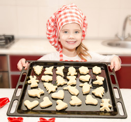 Smiling little girl in chef hat with baking sheet of cookies