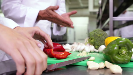 Chef slicing vegetables on a green board