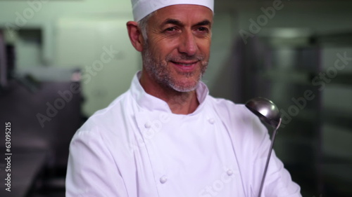 Head chef holding a ladle smiling at camera