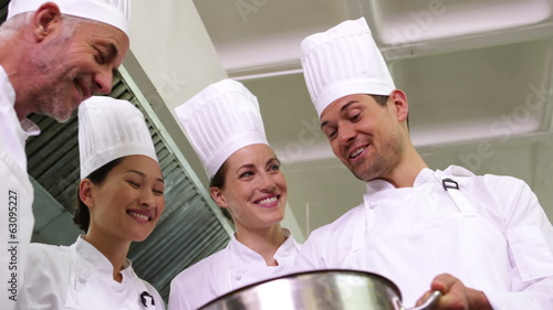 Chef showing colleagues contents of large pot low angle view
