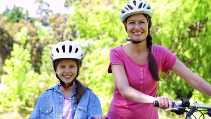 Mother and daughter on a bike ride in the park together