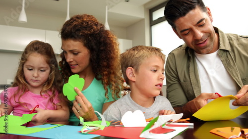 Happy parents and children doing arts and crafts at kitchen