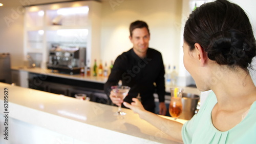Asian woman ordering a cocktail from bartender