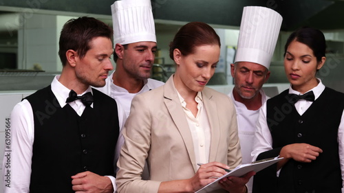 Serious restaurant staff with manager looking at camera