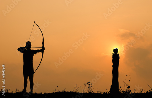 Silhouette archery shoots a bow at an apple on timber