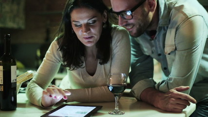 Young couple with tablet computer drinking wine in the kitchen
