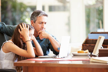 Father Helping Stressed Teenage Daughter Looking At Laptop