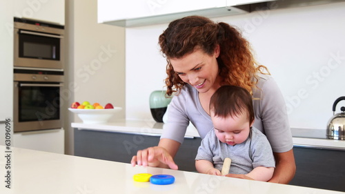 Happy mother sitting with baby boy on lap playing