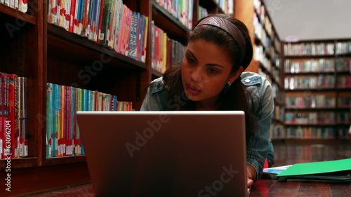 Student lying on floor in library using laptop