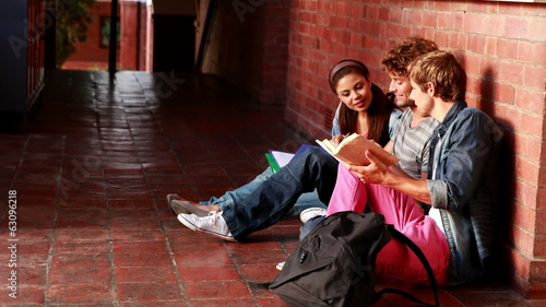Students sitting against wall revising together