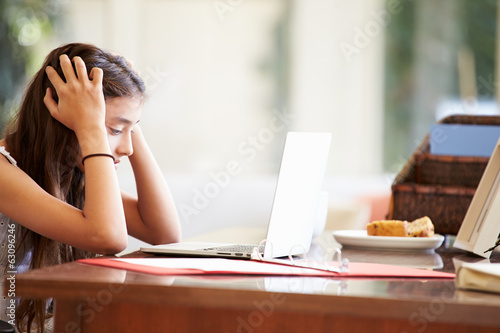 Stressed Teenage Girl Using Laptop On Desk At Home