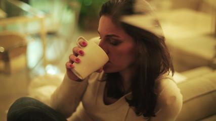 Sad woman drinking tea by the window