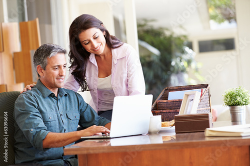 Hispanic Couple Using Laptop On Desk At Home