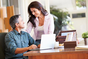Hispanic Couple Using Laptop On Desk At Home