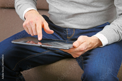 man using his finger to navigate on a digital tablet screen