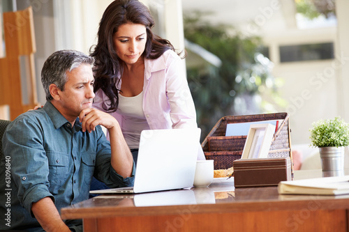 Worried Hispanic Couple Using Laptop On Desk At Home