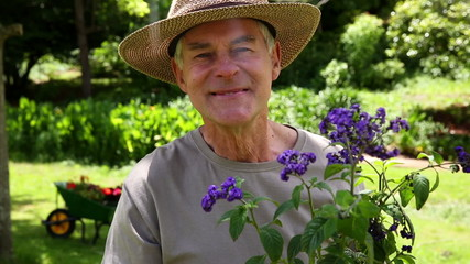 Retired man gardening and smiling at camera