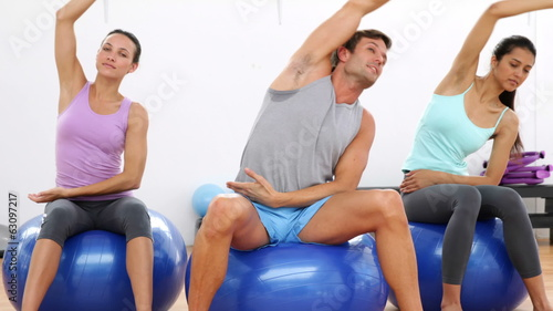 Fitness class sitting on exercise balls stretching