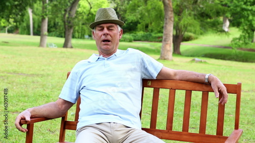Retired man dozing on a park bench