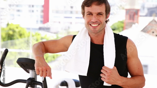 Fit man leaning on exercise bike smiling at camera