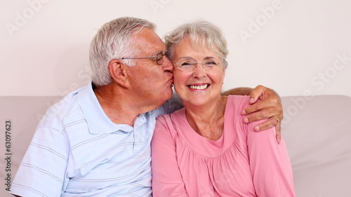 Senior couple sitting on sofa smiling at camera