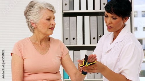 Nurse showing elderly patient how to put on wrist brace