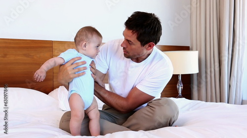 Happy father sitting with baby son on bed