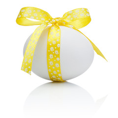 Easter egg with festive yellow bow isolated on white background