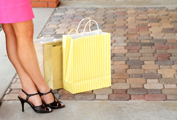 Woman legs taking a break with shopping bags