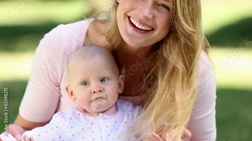 Happy mother holding her baby girl in the park