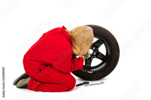 Female car mechanic with wheel