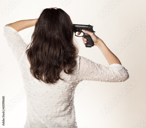 back of the girl holding a pistol at her head