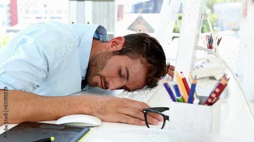 Sleepy designer falling asleep at desk