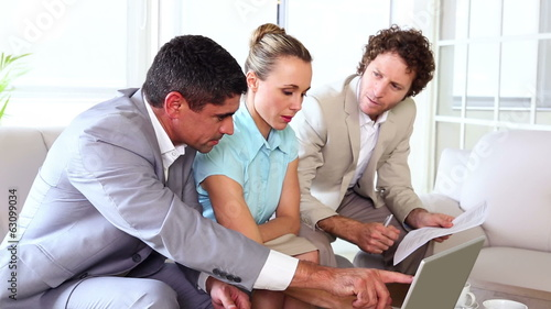 Business people working together on sofa with laptop