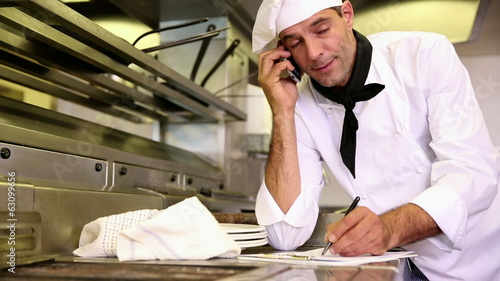 Handsome chef writing on clipboard while talking on phone