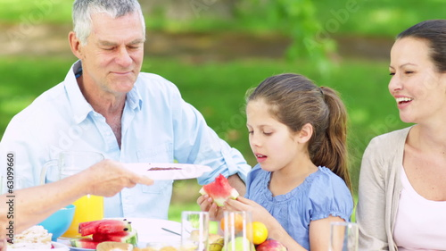 Father serving burgers to his family at a barbecue
