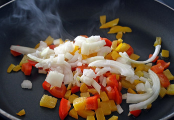 Orange and yellow peppers with onions cooking in skillet