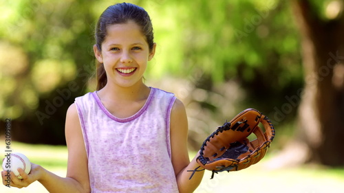 Sporty little girl smiling at camera in the park playing