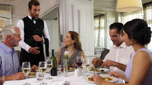 Waiter attending to a table of happy friends