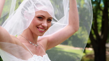Pretty bride smiling at camera and lifting her veil