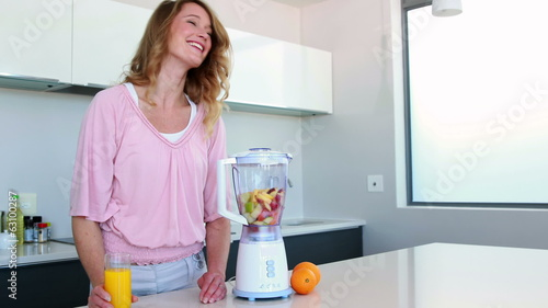 Pretty woman in kitchen drinking orange juice beside juicer