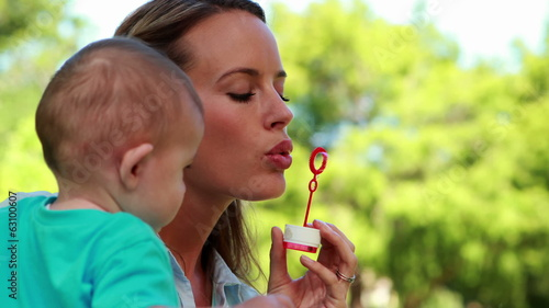 Happy mother blowing bubbles with cute baby son in the park