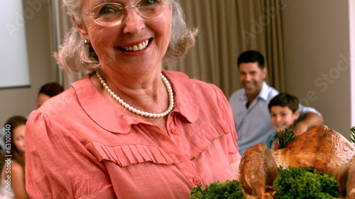 Grandmother holding roast chicken in front of family