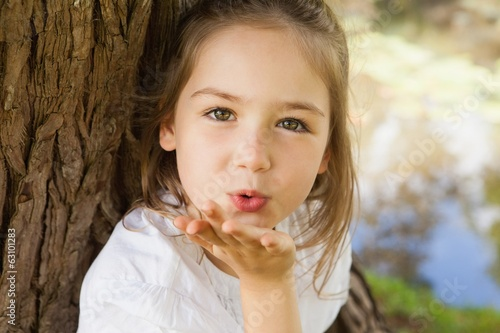 Close-up of a girl blowing a kiss at park